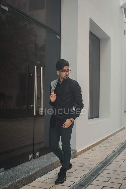 Handsome bearded man in black shirt and eyeglasses walking on urban city street — Stock Photo