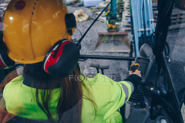 High angle view of woman in hard hat operating industrial vehicle — Stockfoto