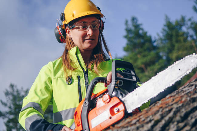 Woman in hard hat and protective goggles holding chainsaw and chopping log — Stockfoto