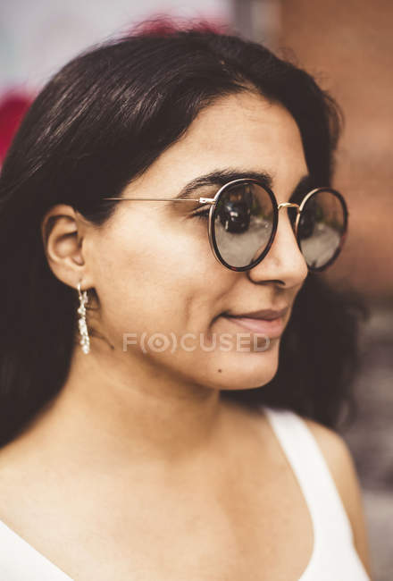 Close-up portrait of beautiful smiling Indian girl in round sunglasses — Stock Photo