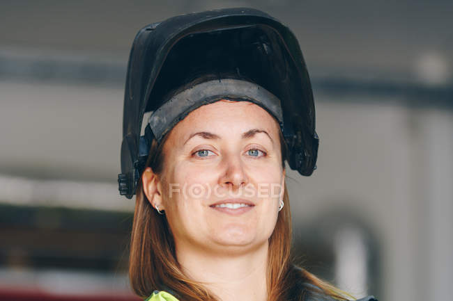 Close-up view of woman wearing black helmet and smiling at camera - foto de stock