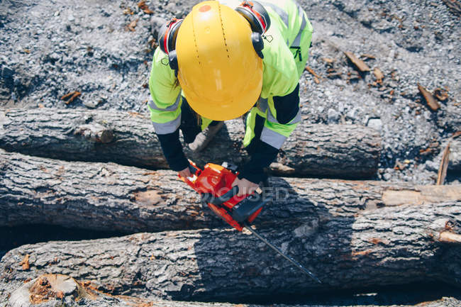 Overhead view of woman in hard hat holding chainsaw and chopping logs — Foto stock