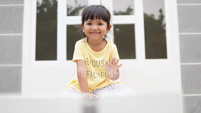 Adorable happy little girl sitting on chair and smiling at camera, selective focus — Stock Photo