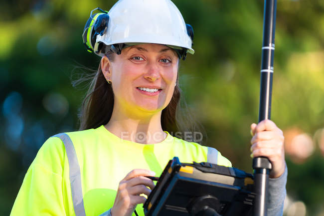 Happy woman in hard hat using technology and smiling at camera — Stockfoto