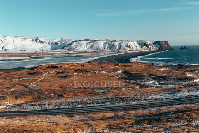 Aerial view of road near sea and snow covered mountain at daytime — Foto stock