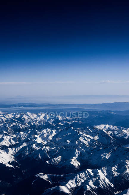 Aerial view of scenic snow-covered mountains and blue sky — стоковое фото