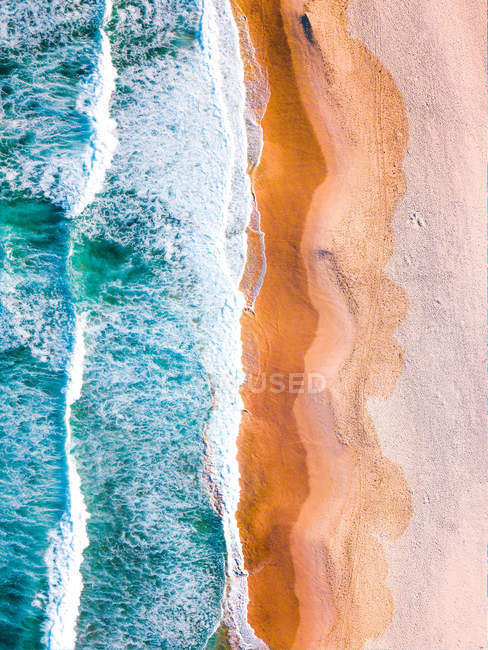 Aerial view of white sandy beach and sea waves — стоковое фото