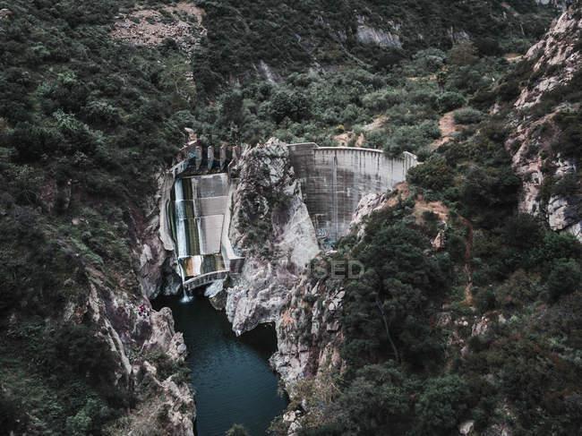 Vista aérea de la presa, el agua y la vegetación verde en las montañas rocosas - foto de stock