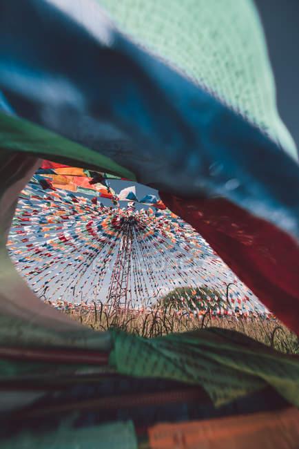 Low angle view of assorted-color textiles against blue sky, selective focus - foto de stock