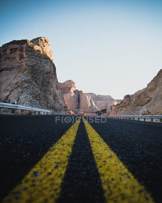 Empty asphalt road with yellow lines and beautiful rocky mountains, low angle view — Foto stock