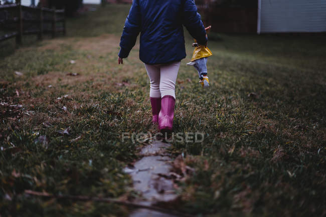 Cropped shot of child in pink rubber boots holding toy and walking on pathway - foto de stock