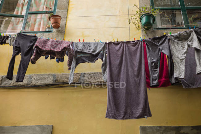 Low angle view of bath towel and clothes hanging on ropes near building — стокове фото
