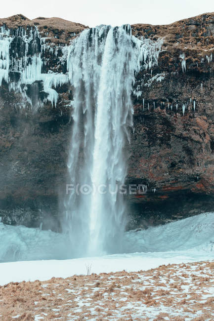 Amazing waterfall on rocky hill and wintertime — стокове фото