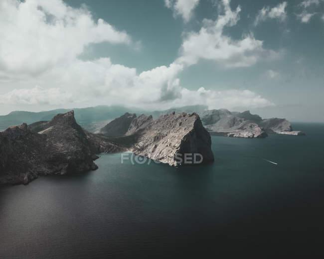 Vista aerea delle scogliere panoramiche in mare sotto il cielo nuvoloso — Foto stock