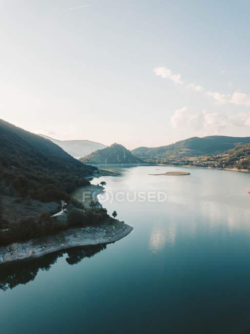 Lago azul cercado por montanhas durante o dia — Fotografia de Stock