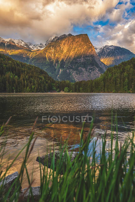 Beautiful calm lake and rocky mountains with snow at sunset — Stock Photo