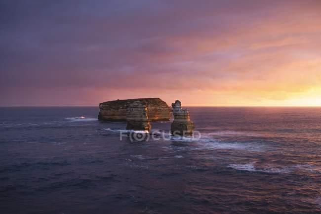Дивовижний морський пейзаж з мальовничими скелями в воді на прекрасному заході сонця — стокове фото