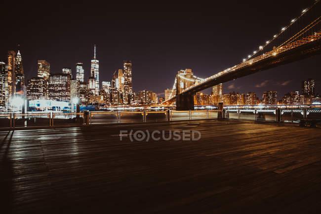 Illuminated bridge and city from deck at night — Stockfoto