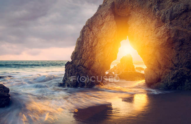 Sun shining through cliff on sea coast at sunset — Fotografia de Stock
