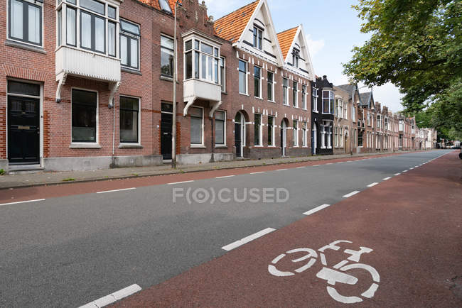 Brown brick houses and empty asphalt road in city during daytime — Stock Photo