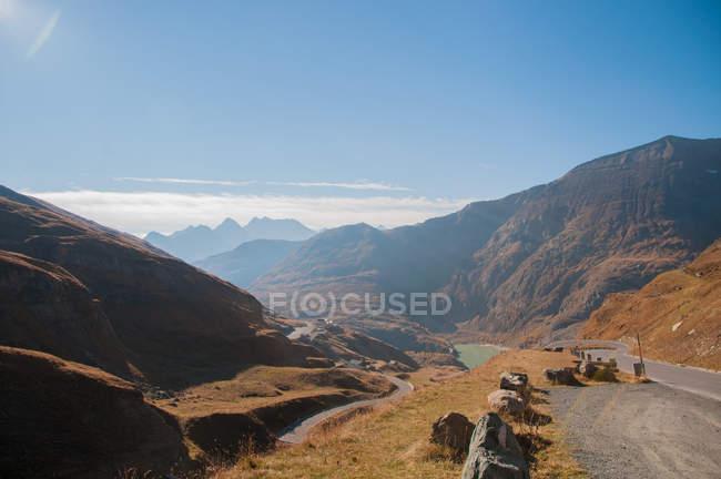 Montanhas, Rio e estrada marrons cénicos durante o dia — Fotografia de Stock