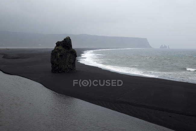 Cliff on black sand at seashore at misty morning — стокове фото