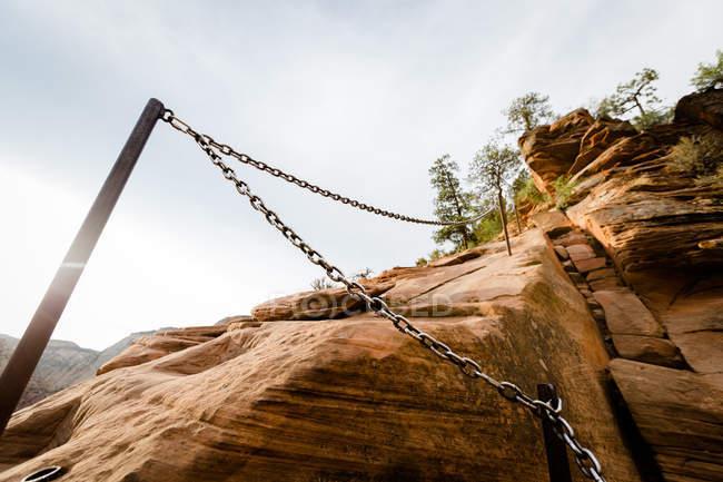 Низький кут огляду сталевого ланцюга в рок в денний час — стокове фото