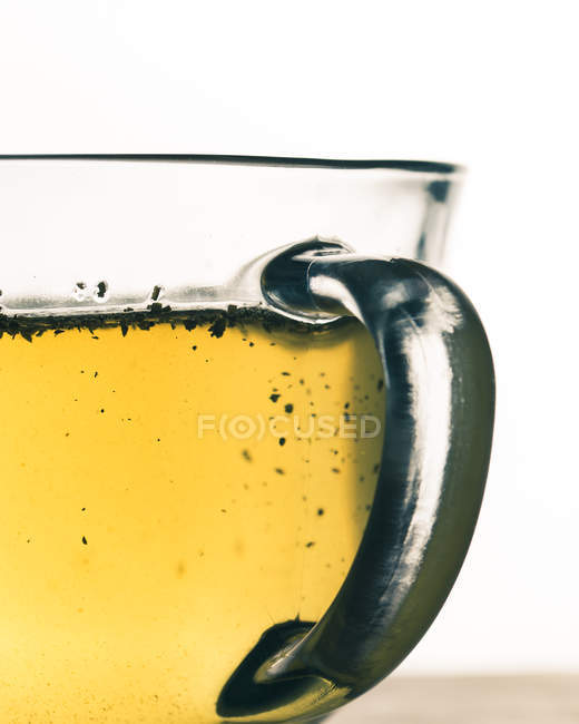 Clear glass mug with yellow liquid on white background, close-up view — стокове фото