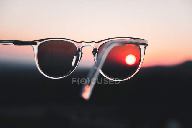 Close-up view of clear glass framed sunglasses at sunset in selective focus photography — Stock Photo