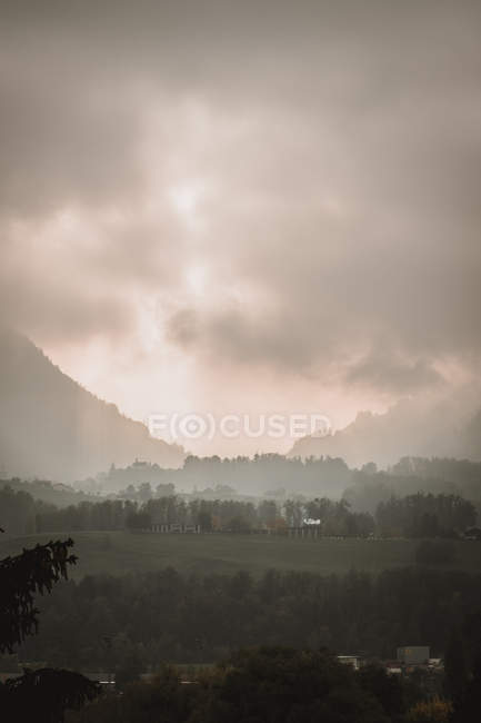 Cloudy sky with thunder and green vegetation on hills — Foto stock