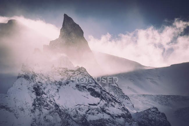 Beautiful rocky mountains covered with snow and cloudy sky — Foto stock