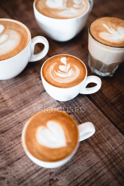 Nahaufnahme von dekorativem Schaum in Kaffee in Glas und weißen Tassen auf Holztisch — Stockfoto
