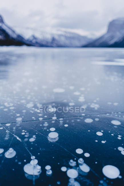 Close-up view of cracks, snow and ice on frozen mountain lake, selective focus — стокове фото