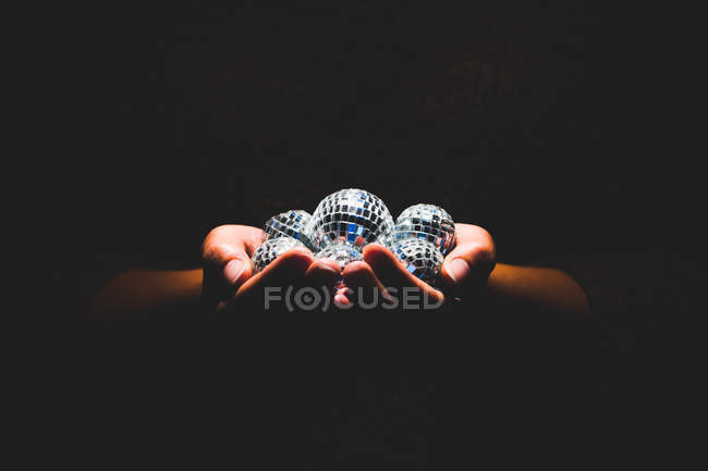 Cropped shot of person holding glitter balls in hands in darkness - foto de stock