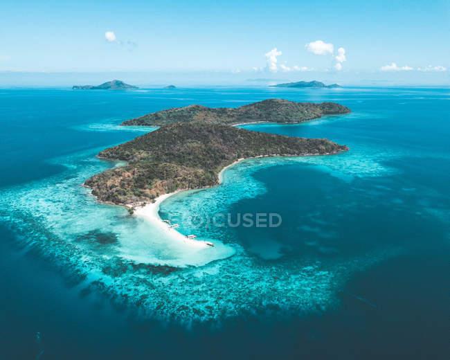 Вид с воздуха на красивый остров, покрытый зеленой растительностью в синем океане — стоковое фото