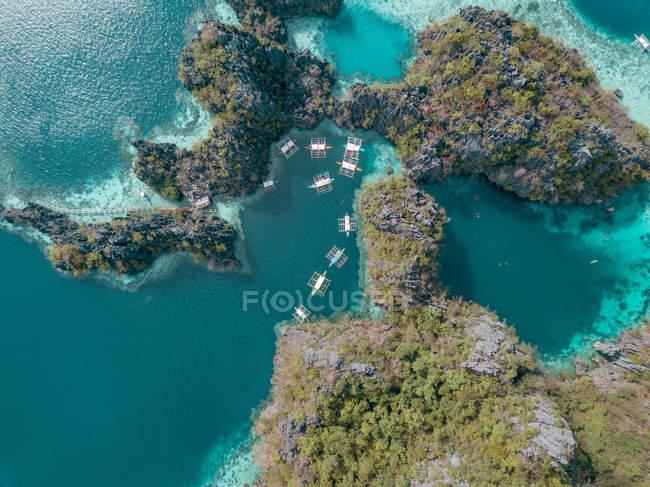 Vue naturelle étonnante des falaises couvertes de végétation verte et des bateaux dans l'eau de mer turquoise, vue aérienne — Photo de stock
