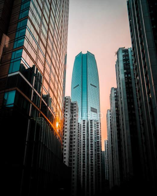 Низький кут огляду сучасних високоповерхових будівель під час заходу сонця — стокове фото