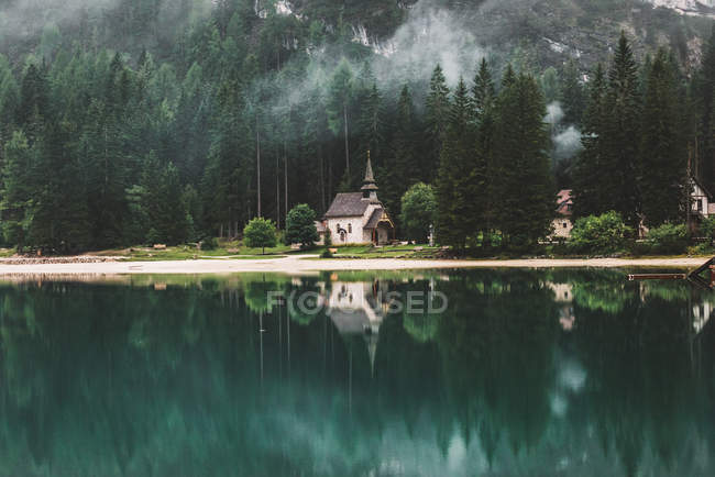 Amazing natural view of buildings and mountain forest reflected in calm lake — Stock Photo
