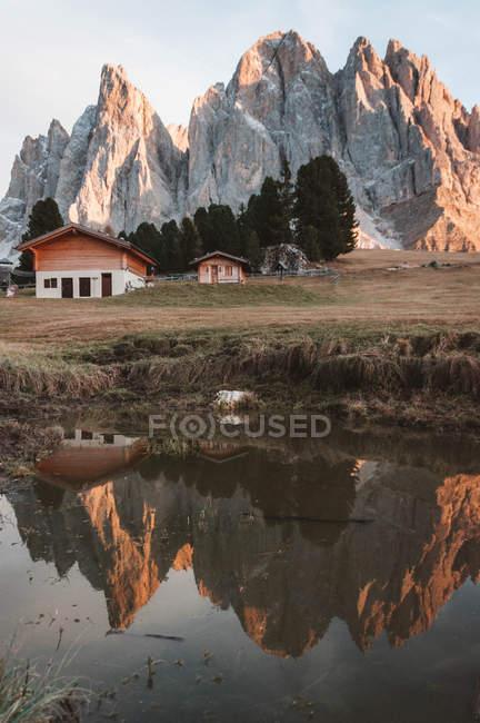 Vista surpreendente das casas e das montanhas rochosas refletidas no lago calmo — Fotografia de Stock