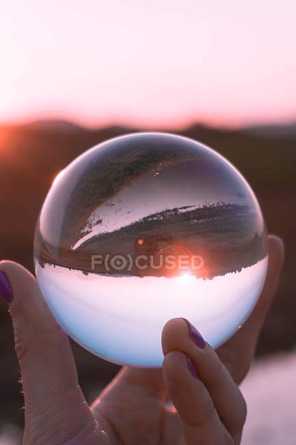 Inverted view of field and sunrise through a glass sphere - foto de stock