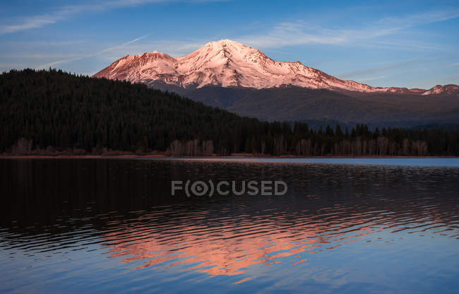 Beautiful green forest and snow-covered mountains reflected in lake — Stock Photo