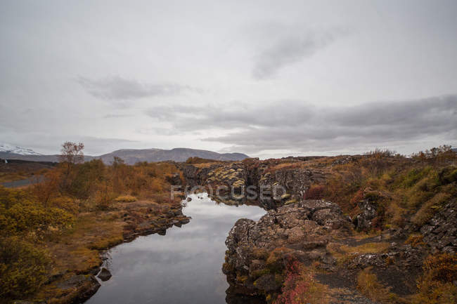 Beautiful landscape with lake near rocks and cloudy sky — Foto stock