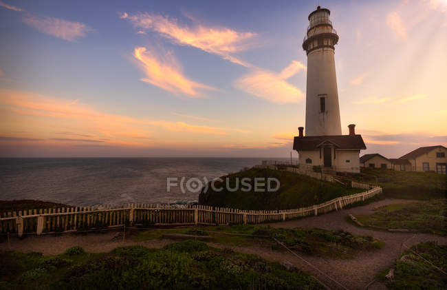 Lighthouse near sea and beautiful sunset sky — Stock Photo