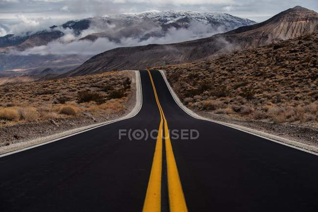 Long wide empty asphalt road and beautiful scenic hills — Foto stock
