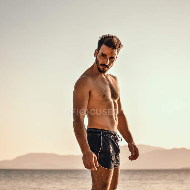 Handsome bearded man with muscled body standing near sea and looking at camera — Stockfoto