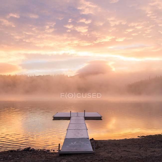 Beautiful landscape with mist on river and empty pier at sunrise — Foto stock