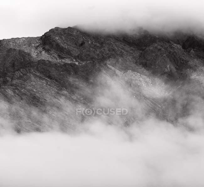 Imagem preto e branco da névoa sobre montanhas rochosas bonitas — Fotografia de Stock