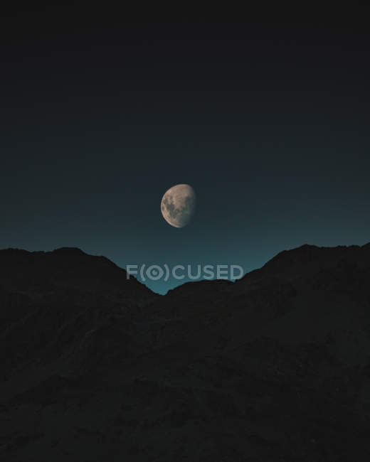 Amazing natural view of Moon between mountains in night sky — Foto stock