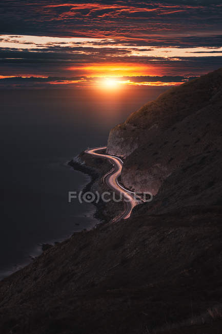 Aerial view of wavy road near mountains and seashore at sunset — Photo de stock
