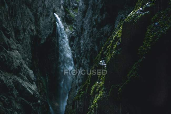 Amazing waterfall in rocky mountains and green moss on foreground — стокове фото